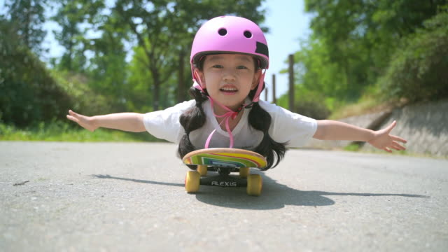 view of a girl riding a skateboard lying down on it - ausgestreckte arme stock-videos und b-roll-filmmaterial