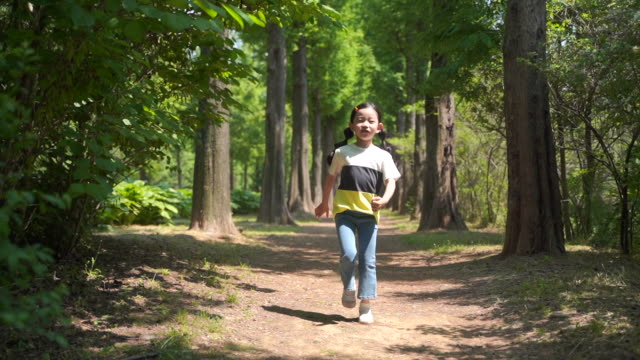 view of a girl running around in the woods - t shirt stock videos & royalty-free footage