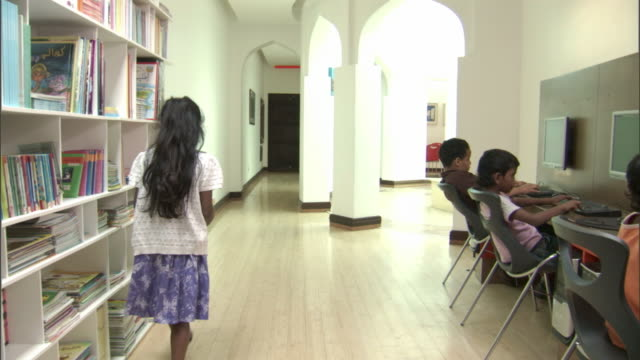 view of a girl taking a book of a library shelf and tracking to kids on computers at the iqra children's library part of the shaikh ebrahim centre. - bookshelf stock videos & royalty-free footage