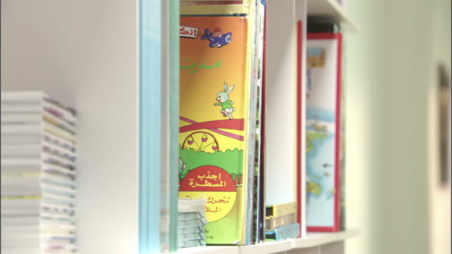 view of a girl's hands pulling an arabic children's book off a library shelf. - bookshelf stock videos & royalty-free footage