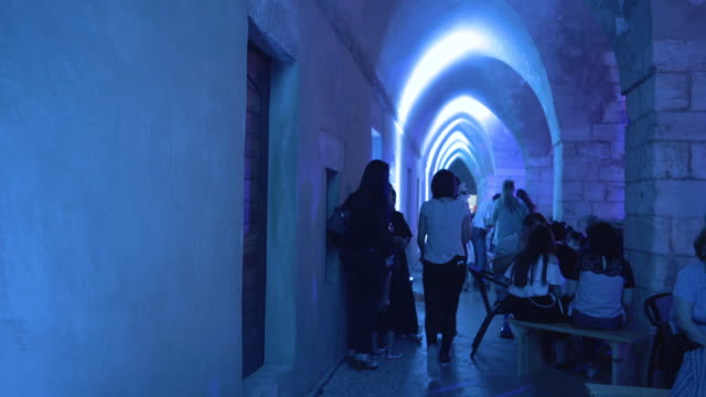 view of a group of lebanese women walking in one of the vaulted corridors of the medieval khan alaskar during a postiftar musical performance at... - religiöse kleidung stock-videos und b-roll-filmmaterial