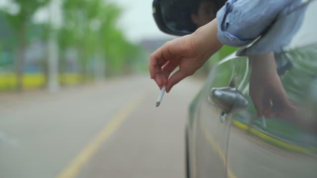 vídeos y material grabado en eventos de stock de view of a hand throwing a cigarette butt from the car - movimiento rápido