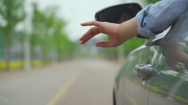 view of a hand throwing a cigarette butt from the car - zigarette stock-videos und b-roll-filmmaterial