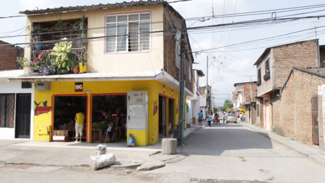 A view of a house on a street corner with a shop in the ground floor with yellow painted walls and a balcony full of plants and flowers on the first...