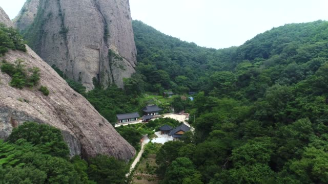 view of a huge boulder and temple in woods, maisan provincial park, jinan-gun - crag stock videos and b-roll footage
