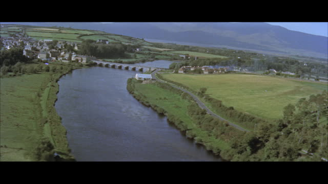 vidéos et rushes de aerial pov view of a irish landscape and sheep running in cultivated fields / ireland - mouton
