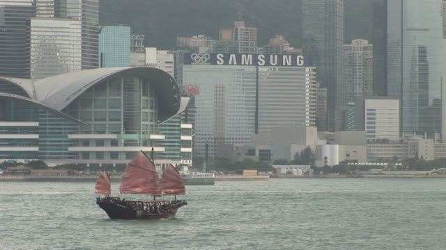 view of a junk cruising in the bay of hong kong china - traghetto star video stock e b–roll