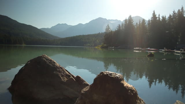 A view of a lake surrounded by mountains and trees