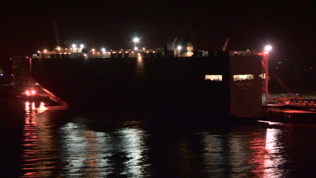 View of a large ship docked in a port at night