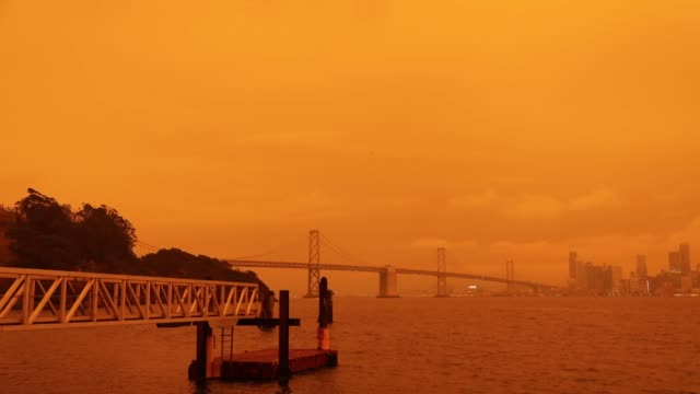 vidéos et rushes de view of a layer of smoke generated by the over 2 dozen wildfires burning in california created and eerie orange glow over mush of the san francisco... - san francisco california