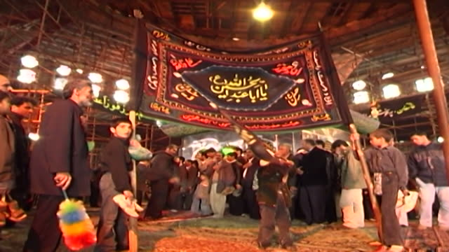 view of a little boy carrying a flag during ashura in a mosque in isfahan province ashura the tenth day of the islamic month of muharram commemorates... - ashura muharram stock videos & royalty-free footage