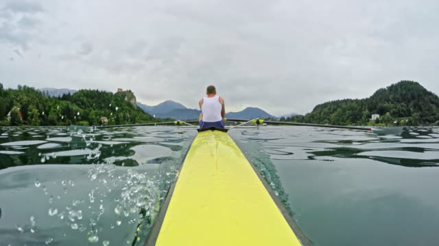 pov  view of a male athlete sculling on a lake from the bow - canottaggio senza timoniere video stock e b–roll