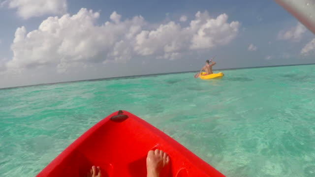 pov view of a man and woman couple kayaking around a tropical island. - human limb stock videos & royalty-free footage