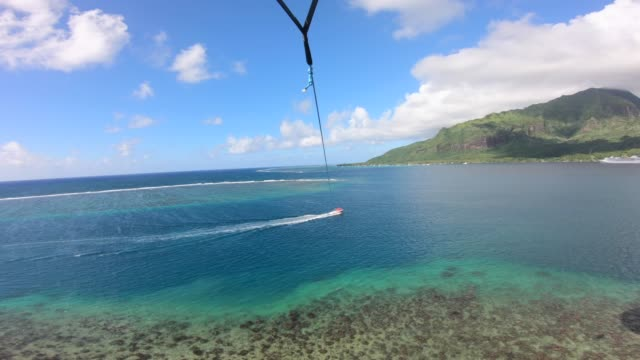 pov view of a man and woman couple parasailing tandem over a tropical island. - kite sailing stock videos & royalty-free footage