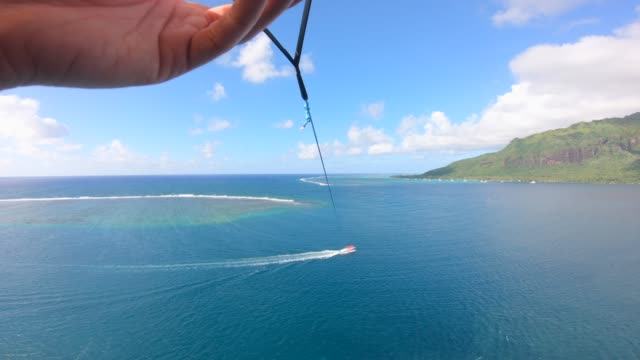 pov view of a man and woman couple parasailing tandem over a tropical island. - フランス海外領点の映像素材/bロール