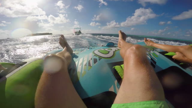 pov view of a man and woman on an inflatable tube towing behind a boat to a tropical island. - 浮き輪点の映像素材/bロール