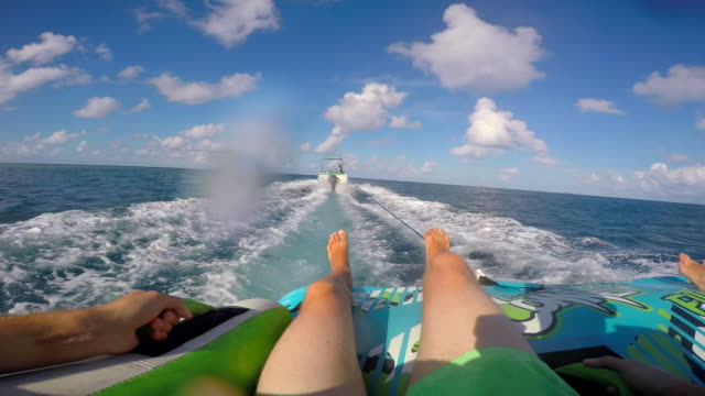 pov view of a man and woman on an inflatable tube towing behind a boat to a tropical island. - rubber ring stock videos & royalty-free footage