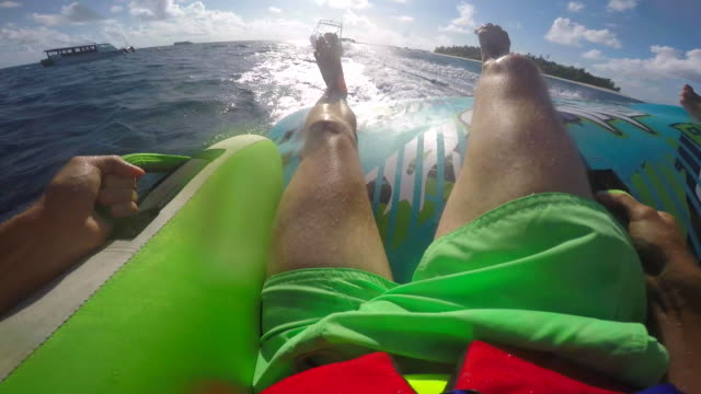 pov view of a man and woman on an inflatable tube towing behind a boat to a tropical island. - inflatable stock videos & royalty-free footage