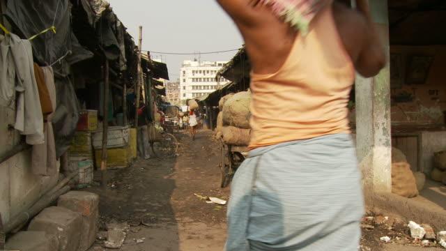 view of a man carrying goods in kolkata, india - ペディキャブ点の映像素材/bロール