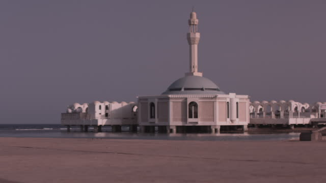 view of a man standing on the beach and looking at the floating rehma mosque on the coast of the red sea in jeddah. - jiddah stock videos & royalty-free footage