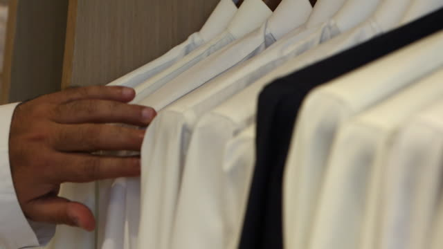 view of a man's hand touching a row of white thobes on hangers - dish dash stock videos & royalty-free footage