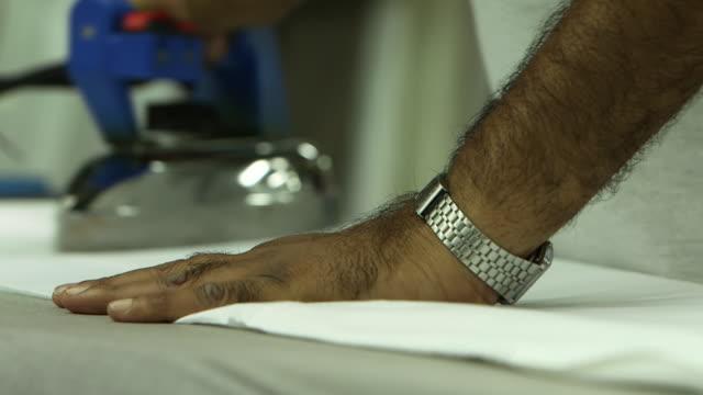 view of a man's hands ironing. - maßkonfektion stock-videos und b-roll-filmmaterial