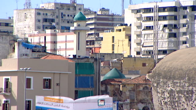 view of a minaret amongst newly renovated and old, bullet-ridden buildings in downtown beirut. lebanon's 15-year civil war left permanent marks on... - contrasts stock videos & royalty-free footage