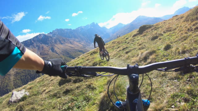 pov view of a mountain biker hands handlebars biking on a singletrack trail. - schweiz stock-videos und b-roll-filmmaterial