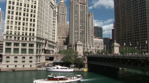 view of a moving boat near wrigley building and tribune tower in chicago united states - torre del tribune video stock e b–roll