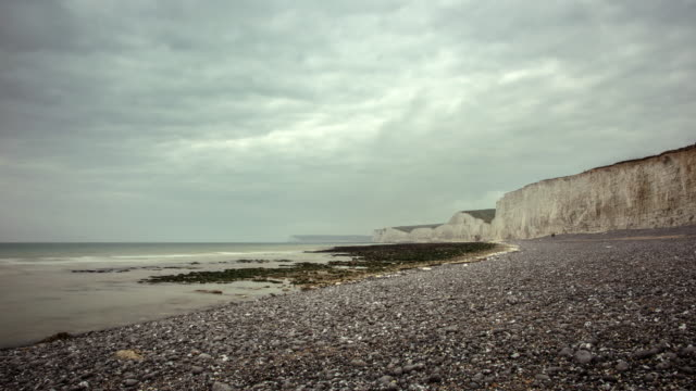 View of a pebble Beach and the white chalk cliffs of the Seven Sisters on the South Coast an overcast sky passes over the Channel