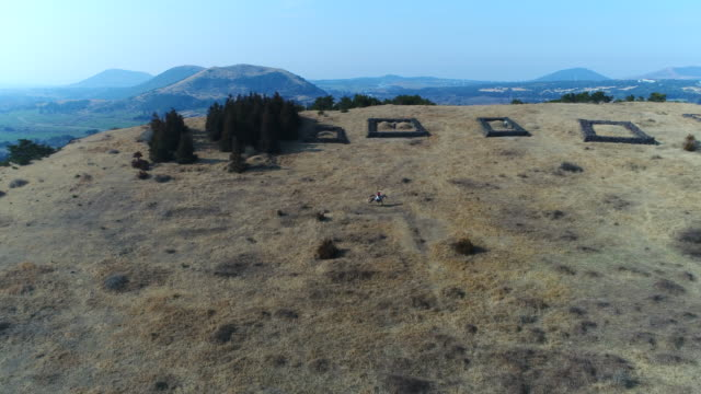 view of a person riding horse around graves in oreum parasitic cone / jeju-do, south korea - recreational horse riding stock videos & royalty-free footage