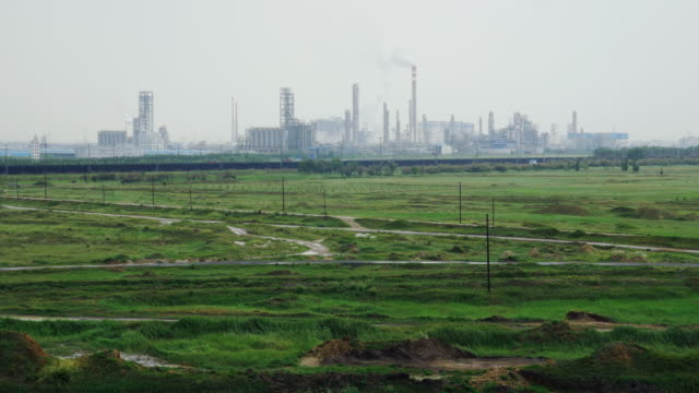 view of a petroleum refinery close to the radioactive toxic tailings lake at the rear of the baogang iron and steel plant in baotou china the lake is full of heavy metals and rare earths and over 10km wide - oil refinery stock videos & royalty-free footage