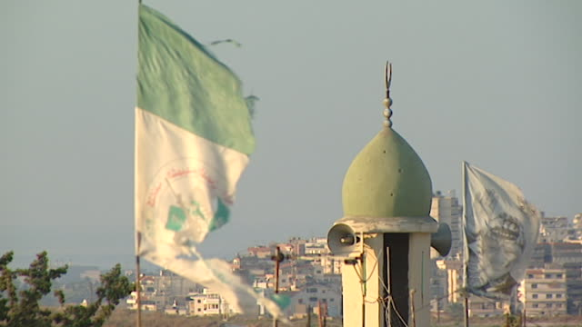 view of a plo flag with the picture of yasser arafat fluttering in the breeze next to a mosque minaret in the mieh mieh palestinian refugee camp near... - palestine liberation organisation stock videos & royalty-free footage