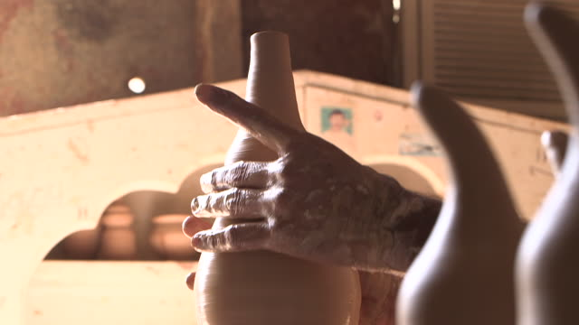 view of a potter's hands working clay on a wheel to form a vase. - moulding a shape stock videos & royalty-free footage