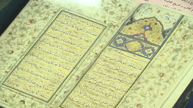 view of a qoranic surah in arabic calligraphy with a floral decorative border in an illuminated antique qoran in the marachi najafi library... - capital letter stock videos & royalty-free footage