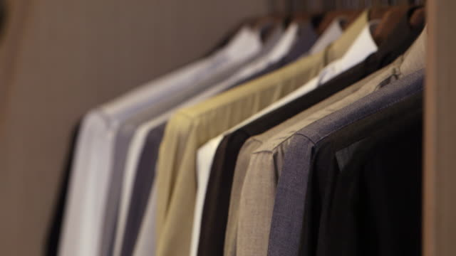 view of a row of thobes on hangers. - tailored clothing stock videos & royalty-free footage