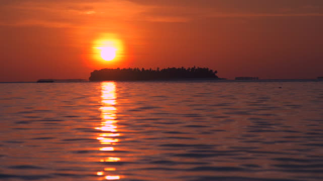 vidéos et rushes de view of a scenic tropical island at sunset in the maldives. - partie d'une série