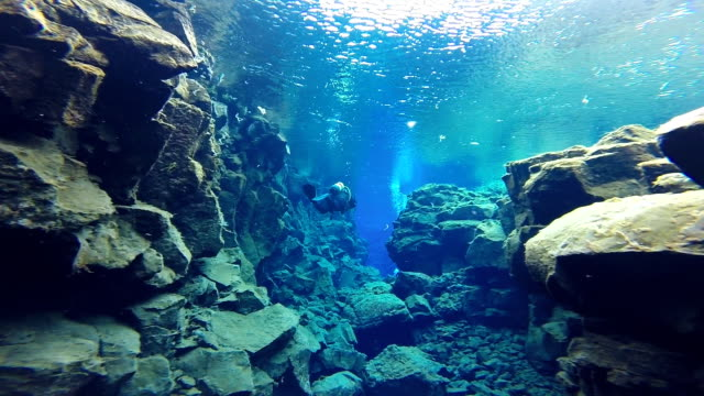 View of a scuba diver swimming through the wider section of the Silfra Fissure in Thingvellir National Park Iceland.