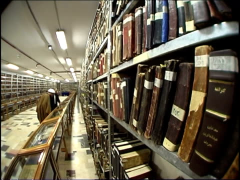 view of a sheikh viewing the book ancient books and manuscripts in one of the rooms of the hawza ilmiya islamic library in qom. - orthographic symbol stock videos & royalty-free footage