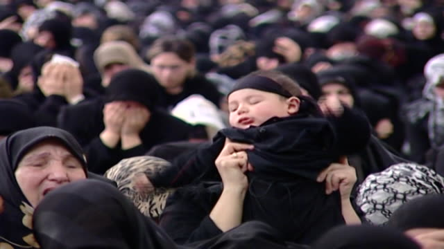 vídeos y material grabado en eventos de stock de view of a shiite women holding up her baby who is wearing a mourning bandana. ashura commemorates the death of hussain ibn ali at the battle of... - ashura