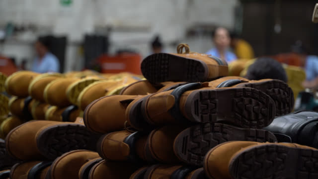view of a shoe factory and close up on leather boots - stack stock videos & royalty-free footage