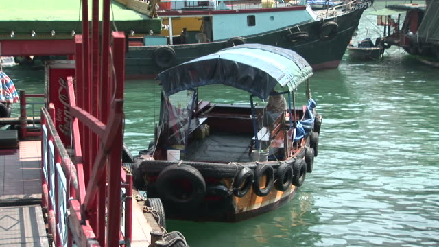 view of a small boat anchored in hong kong china - anchored stock videos & royalty-free footage