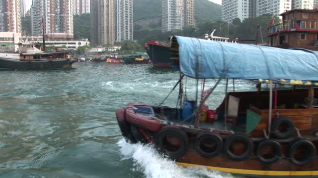 vídeos y material grabado en eventos de stock de view of a small boat cruising in hong kong china - pasear en coche sin destino