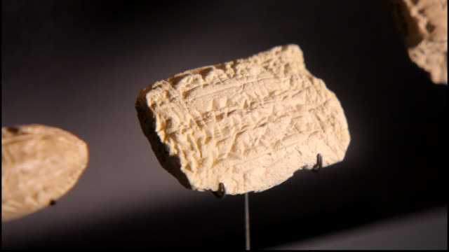 view of a small clay tablet or seal impressed with ancient cuneiform writing, at the bahrain national museum. - 足根点の映像素材/bロール