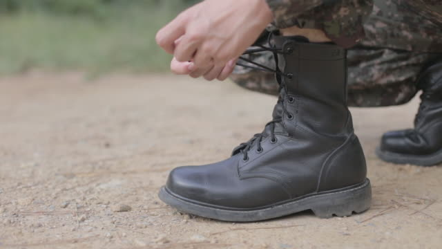 view of a soldier adjusting military boots - south korea stock videos & royalty-free footage