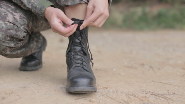 View of a soldier adjusting military boots