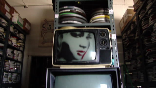 view of a stack of old television sets and shelves full of film canisters in the background in a film archive in san francisco, california on... - film reel stock videos & royalty-free footage