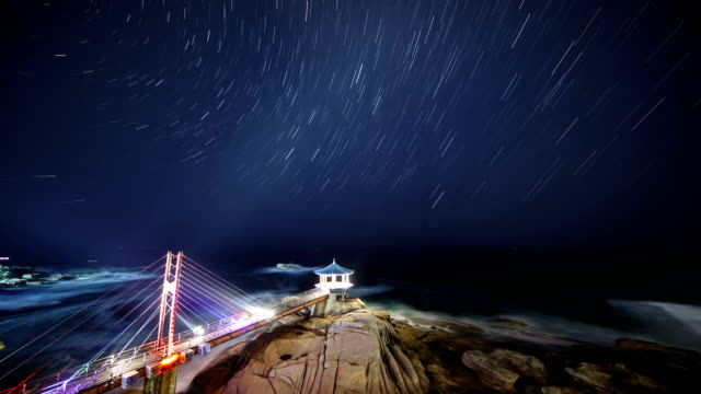 vídeos de stock, filmes e b-roll de view of a star field over yeonggeumjeong (observation point) in dongmyeong-port, sokcho (famous travel destination for summer vacation) at night - chuva de meteoros
