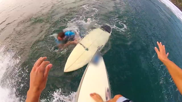 pov view of a surfer crashing while surfing into another surfer, riding over his surfboard. - slow motion - extremsport perspektive stock-videos und b-roll-filmmaterial