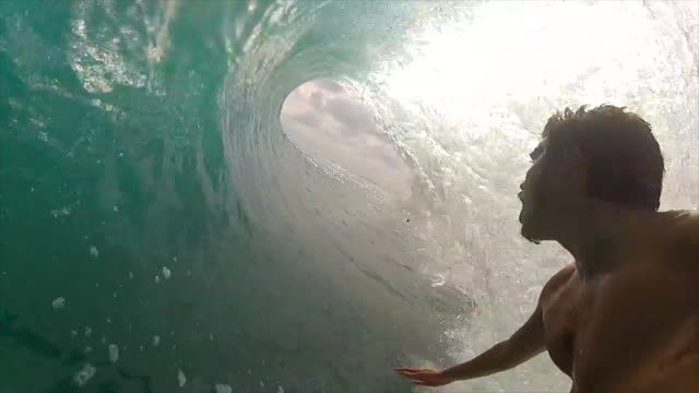 pov view of a surfer surfing inside waves and getting tubed on a surfboard. - slow motion - surfing stock videos & royalty-free footage
